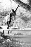 Chica joven que miente en un barco que flota en el lago Foto de archivo libre de regalías