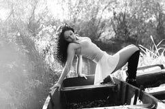 Chica joven que miente en un barco que flota en el lago Fotografía de archivo