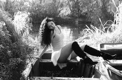 Chica joven que miente en un barco que flota en el lago Fotografía de archivo libre de regalías