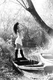 Chica joven que miente en un barco que flota en el lago Imagenes de archivo