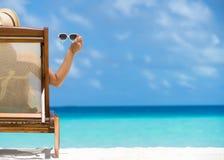 Chica joven que miente en un ocioso de la playa con los vidrios a disposición Imagen de archivo libre de regalías