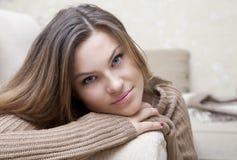 Chica joven que miente en un sofá Fotos de archivo