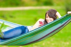 Chica joven que miente en una hamaca con el teléfono celular Fotografía de archivo