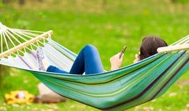 Chica joven que miente en una hamaca con el teléfono celular Fotos de archivo libres de regalías