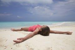 Chica joven que miente en una playa blanca de la arena por el océano Imagen de archivo