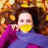 Chica joven que miente entre las hojas de otoño, labios de ocultación detrás de una hoja Imágenes de archivo libres de regalías