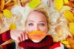 Chica joven que miente entre las hojas de otoño, labios de ocultación detrás de una hoja Foto de archivo