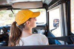 Chica joven que mira alrededor en coche del offroader durante viaje del safari fotos de archivo