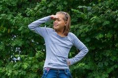Chica joven que mira alrededor en jardín Fotografía de archivo