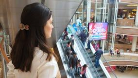 Chica joven que mira del último piso en gente en el centro comercial almacen de metraje de vídeo