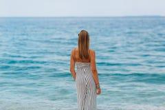 Chica joven que mira el mar que se coloca en la playa Fotos de archivo