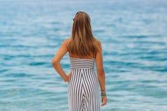 Chica joven que mira el mar que se coloca en la playa Fotos de archivo libres de regalías