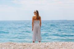 Chica joven que mira el mar que se coloca en la playa Imagenes de archivo