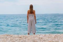 Chica joven que mira el mar que se coloca en la playa Imagen de archivo libre de regalías