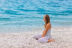 Chica joven que mira el mar que se coloca en la playa Imagen de archivo