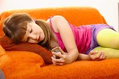 Chica joven que mira el teléfono móvil Imágenes de archivo libres de regalías