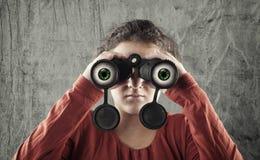 Chica joven que mira el throush un binocular Imagenes de archivo