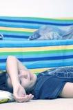 Chica joven que mira el tinte del azul de la TV Imagenes de archivo