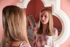 Chica joven que mira en el espejo Imagenes de archivo
