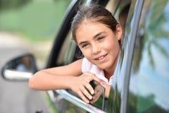 Chica joven que mira fijamente hacia fuera la ventanilla del coche Imágenes de archivo libres de regalías