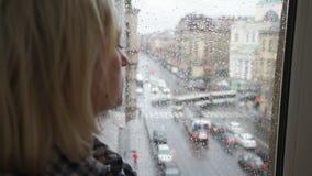 Chica joven que mira hacia fuera la ventana en un día lluvioso almacen de video