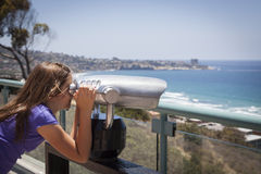 Chica joven que mira hacia fuera sobre el Océano Pacífico con el telescopio Fotos de archivo