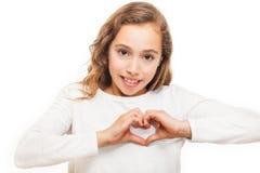 Chica joven que mira la cámara que muestra gesto del corazón con dos manos aisladas fotografía de archivo