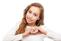 Chica joven que mira la cámara que muestra gesto del corazón con dos manos aisladas imagen de archivo libre de regalías