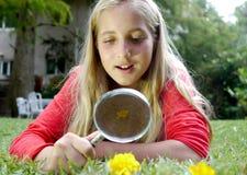 Chica joven que mira la flor Imágenes de archivo libres de regalías