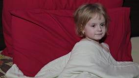 Chica joven que mira la televisión de la TV en la cama almacen de video