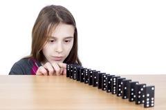 Chica joven que mira los dominós negros alineados en el tablero de madera aislado en blanco Foto de archivo libre de regalías