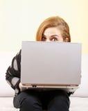 Chica joven que mira sobre la computadora portátil Fotografía de archivo libre de regalías