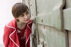 Chica joven que mira a través de la puerta Foto de archivo libre de regalías