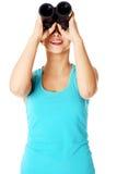 Chica joven que mira a través de los prismáticos. Imagenes de archivo