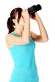 Chica joven que mira a través de los prismáticos. Imagen de archivo