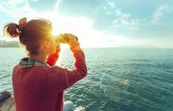 Chica joven que mira a través de los prismáticos el mar en Sunny Day brillante, vista posterior Concepto del viaje del viaje de l Fotos de archivo