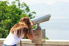 Chica joven que mira a través de los prismáticos públicos la playa imagenes de archivo