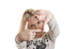 Chica joven que mira a través de sus manos Foto de archivo libre de regalías