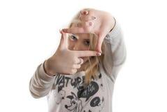 Chica joven que mira a través de sus manos imagen de archivo