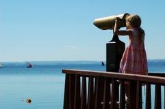 Chica joven que mira a través del telescopio Fotos de archivo libres de regalías