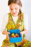Chica joven que mira un rectángulo con los huevos de Pascua Fotografía de archivo