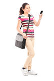 Chica joven que mira un teléfono celular Imágenes de archivo libres de regalías
