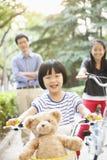 Chica joven que monta su bicicleta con su familia Foto de archivo