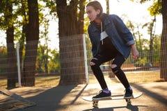 Chica joven que monta un monopatín skateboarding Al aire libre, forma de vida Imagen de archivo libre de regalías