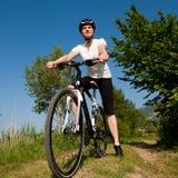 Chica joven que monta una bici campo a través Imagenes de archivo
