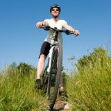 Chica joven que monta una bici en un camino del campo Foto de archivo libre de regalías