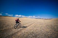 Chica joven que monta una bicicleta en las montañas Fotografía de archivo
