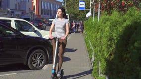 Chica joven que monta una vespa eléctrica en el camino en la ciudad, MES lento