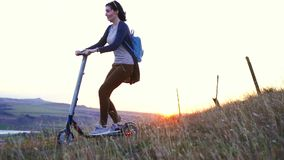 Chica joven que monta una vespa eléctrica en una montaña en la puesta del sol, MES lento almacen de video