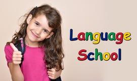 Chica joven que muestra el pulgar para arriba con la escuela de idiomas del texto imágenes de archivo libres de regalías